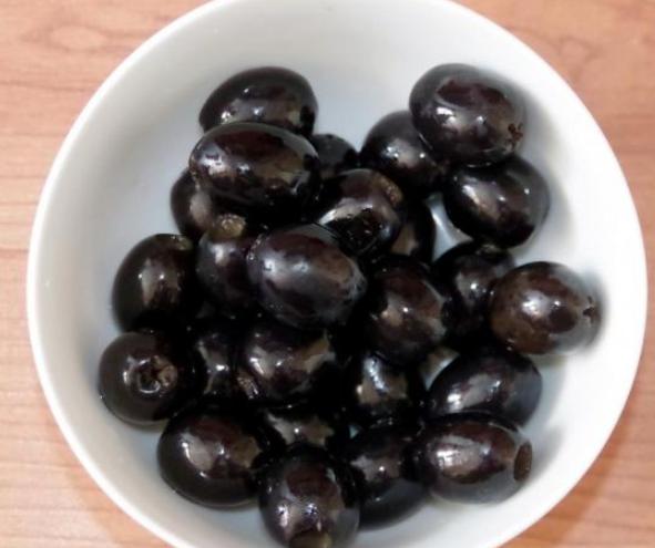 Открыть банку с маслинами и вылить рассол, высыпать в удобную тару