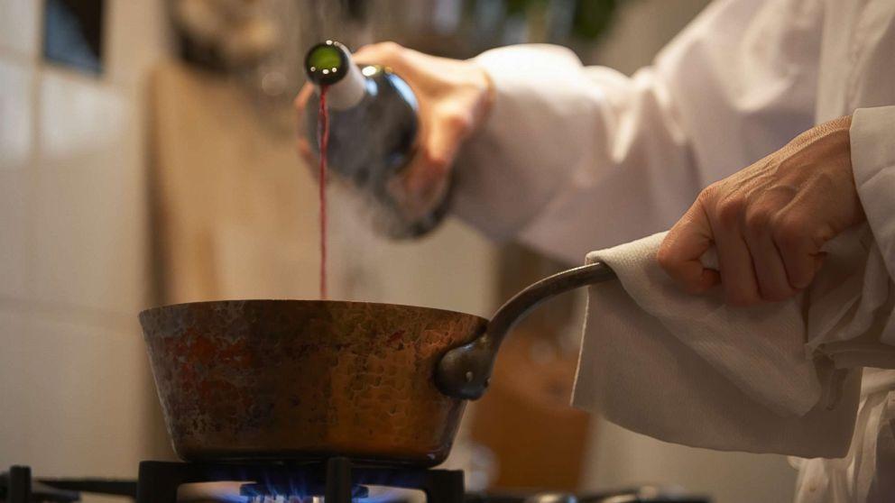 В глубокую сковороду вылейте вино и воду,
